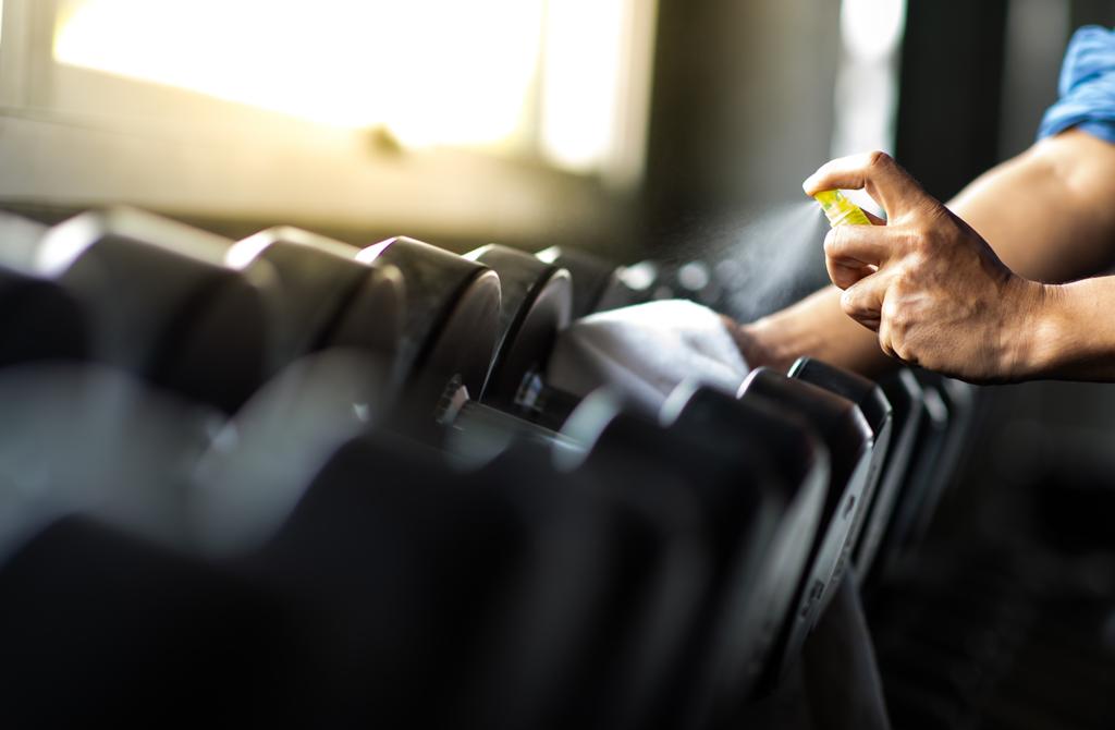 Gym employee spraying cleaner on dumbells