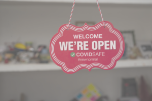 Pink We are open sign in a store window
