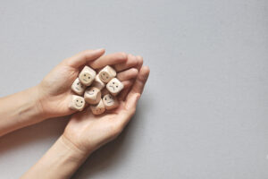 Two hands holding dice with negative and positive faces on them