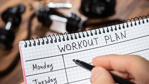 Person filling out a workout plan