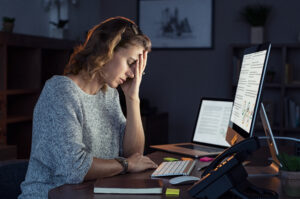 Woman experiencing stress and burnout while working on a computer